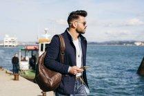 Homem com a mochila e smartphone em pé na porta — Fotografia de Stock