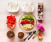 Postres dulces arreglados y tazón de fruta saludable en la mesa con rosa - foto de stock