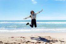 Woman jumping on sandy beach — Stock Photo