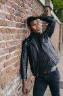 Черный человек опирается на кирпичную стену — стоковое фото