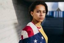 Donna pensierosa avvolta nella bandiera USA — Foto stock