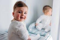 Bébé garçon assis devant un miroir — Photo de stock