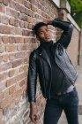 Preto homem encostado no tijolo parede — Fotografia de Stock