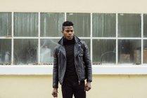 Homem negro de pé contra a construção — Fotografia de Stock