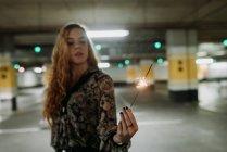 Mujer joven de pie en el estacionamiento con luces de Bengala - foto de stock