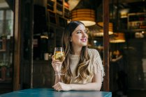 Женщина с напитком, сидя в кафе — стоковое фото