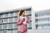 Женщина в розовом костюме с кофе и смартфоном — стоковое фото