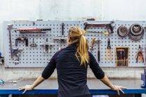 Жінка, стоячи в механічних майстерень — стокове фото