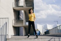 Sporty woman standing in front of building — Stock Photo
