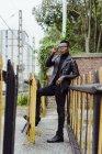 Чорна людина, спираючись на паркан — стокове фото