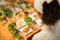 Mujer que sirve platos con bocadillos veganos - foto de stock
