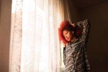 Femme debout à côté de la fenêtre — Photo de stock