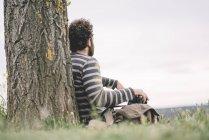 Männlicher Fotojournalist sitzt mit Kamera — Stockfoto