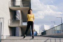 Donna sportiva in piedi di fronte all'edificio — Foto stock