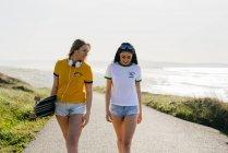 Teenage girls with longboard walking on road — Stock Photo