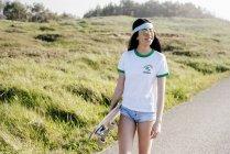 Adolescente com longboard andando na estrada — Fotografia de Stock