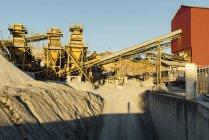 Equipamento industrial e maquinaria em pedreira na luz solar — Fotografia de Stock