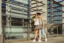 Couple with skateboard kissing on street — Stock Photo