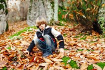 Jungen spielen mit trockenen Blättern — Stockfoto