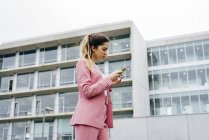 Woman in pink suit using smartphone — Stock Photo