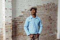 Preto homem de pé contra tijolo parede — Fotografia de Stock