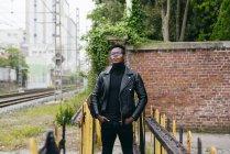 Negro hombre de pie en la barandilla - foto de stock