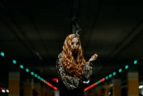 Pretty redhead woman having smoke on blurred parking lot. — Stock Photo