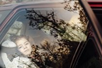 Girl sitting in car and looking through window — Stock Photo