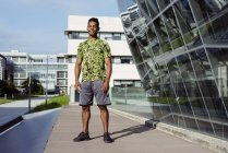 Handsome sporty ethnic man standing in city with modern buildings on background — Stock Photo