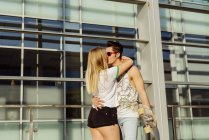Couple with skateboard in front of building — Stock Photo