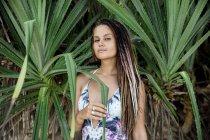 Mujer de pie en plantas tropicales - foto de stock