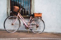 Rosa dipinto arrugginito bicicletta d'epoca parcheggiata alla finestra sulla strada — Foto stock