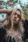 Ritratto di donna bionda in fiori che tocca la testa — Foto stock