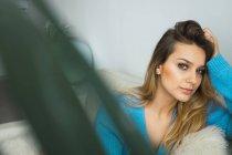 Портрет молодой женщины, отдыхающей на диване дома — стоковое фото