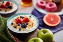 Bowl of fresh yogurt topped with berries and cornflakes on board — Stock Photo