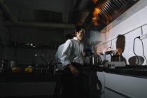 Кука, роблячи за фламбе в кухні ресторану з колегою на тлі — стокове фото