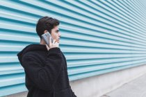 Young teenager standing at metal wall and talking on smartphone on street — Stock Photo