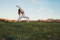 Mujer en forma estiramiento en el césped en la naturaleza - foto de stock