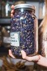 Mãos femininas segurando jarra de temperos — Fotografia de Stock
