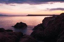 Côte rocheuse et ciel dramatique au coucher du soleil — Photo de stock