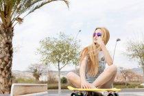 Блондинка, сидящая на земле с доской — стоковое фото