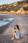 Вдумчивая молодая женщина в купальнике сидит на пляже — стоковое фото
