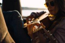 Стильний жінка з гітарою, сидячи в машині в природі — стокове фото
