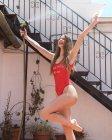 Тощая красивая молодая женщина в красном купальнике веселится на заднем дворе с брызгающим водой шлангом на солнце — стоковое фото