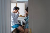 Young couple in pajamas drinking from cups in kitchen — Stock Photo