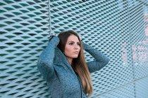 Ritratto di giovane donna in abiti sportivi in piedi davanti alla rete blu — Foto stock