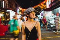Stylish young pretty Asian woman walking on illuminated street at night and looking away — Stock Photo