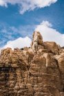 Desde abajo roca áspera con piedras en la parte superior y cielo azul nublado. - foto de stock