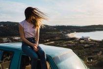 Donna con agitando i capelli che si siede sul tetto dell'auto sulla costa — Foto stock