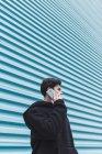 Jovem adolescente em pé na parede de metal e falando no smartphone na rua — Fotografia de Stock